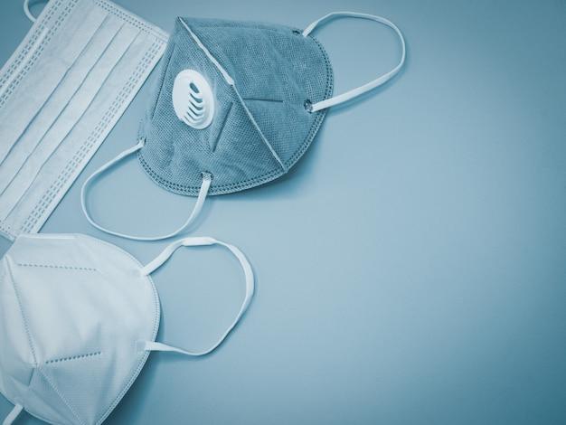 Se coloca una variedad de máscaras sobre un fondo gris con espacio para copiar texto como herramienta principal de prevención durante la crisis covid-19. concepto de autoprotección y asistencia sanitaria