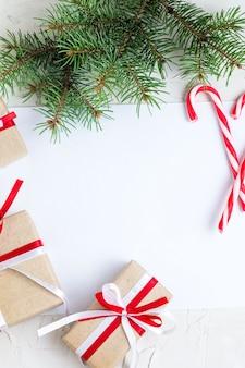 Colocación de papel transparente con bastón de caramelo, ramas de árboles de navidad y regalos