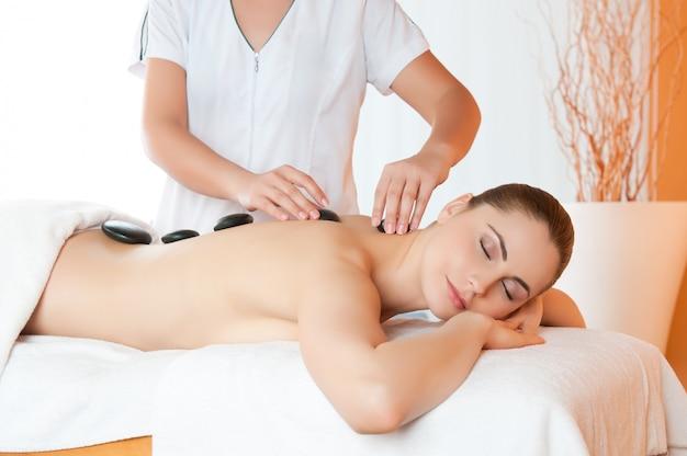 Colocación de piedras calientes en la espalda para la última terapia en el centro de spa