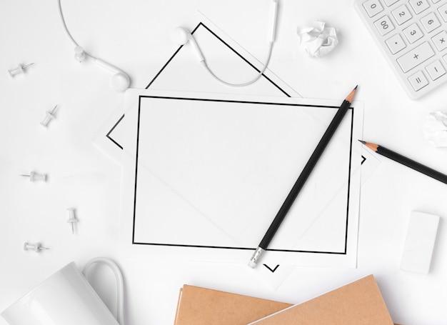 Colocación plana de los accesorios del espacio de trabajo de escritorio con una hoja de papel en blanco sobre fondo blanco