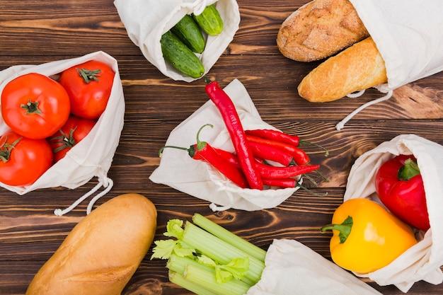 Colocación plana de bolsas reutilizables en superficie de madera con frutas y verduras.