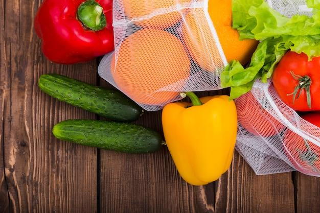 Colocación plana de bolsas reutilizables en superficie de madera con verduras y frutas.