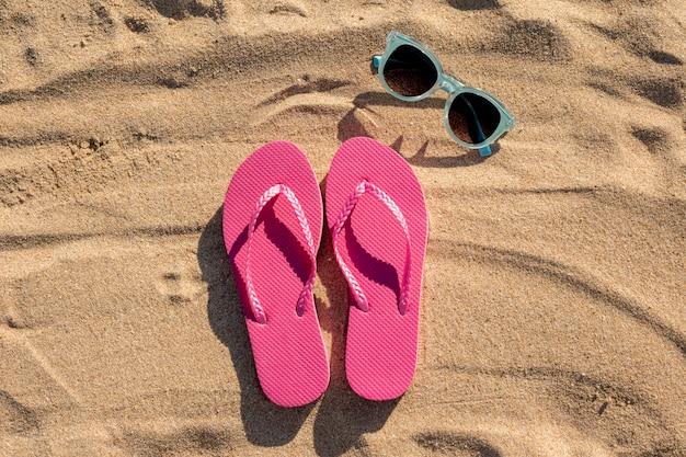 Colocación plana de chanclas y gafas de sol sobre arena.