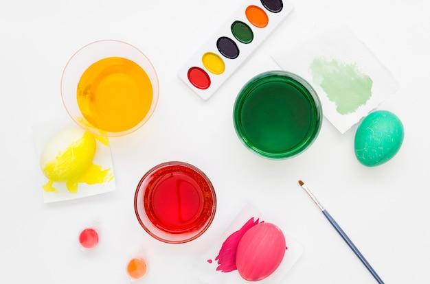 Colocación plana de colorantes coloridos para huevos de pascua con paleta y pincel