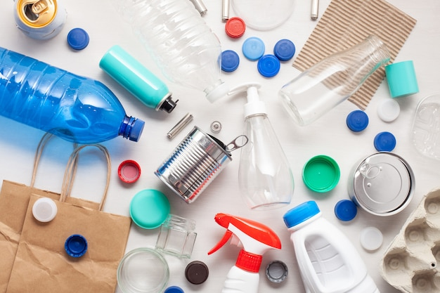 Colocación plana de diferentes desechos, desechos listos para reciclar. plástico, vidrio, papel, latas.