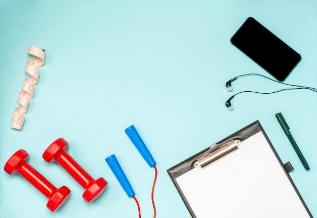 Colocación plana de equipamiento deportivo para fitness en una superficie azul