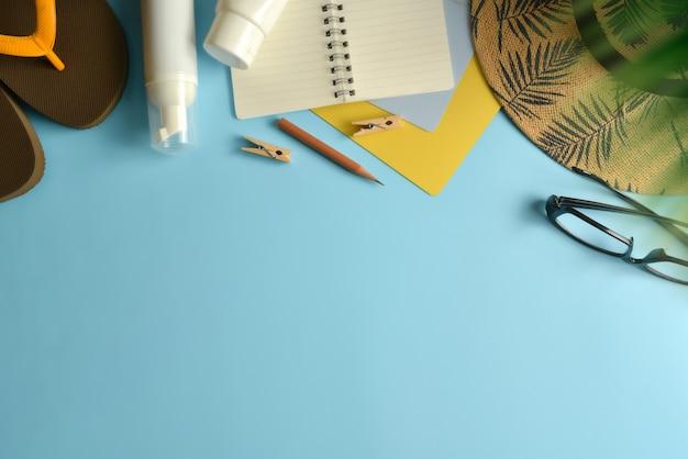 Colocación plana, espacio de trabajo de vista superior con sombrero, bloqueador solar sobre fondo azul.