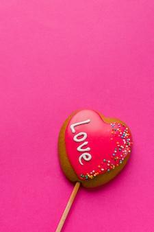 Colocación plana de galleta en forma de corazón en el palo y espacio de copia