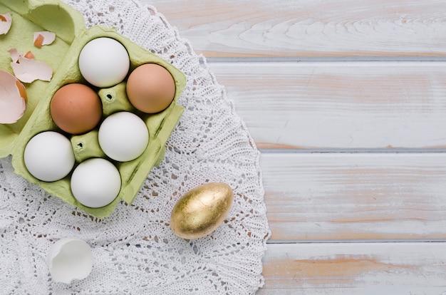 Colocación plana de huevos de pascua en cartón en tapete con espacio de copia