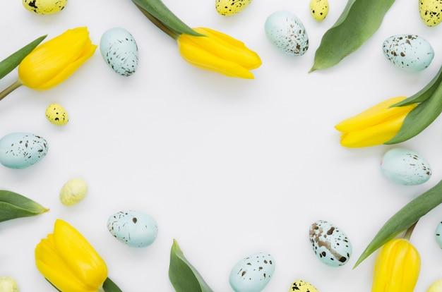 Colocación plana de huevos de pascua con marco de tulipanes