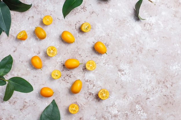 Colocación plana de kumquats sobre una superficie de concreto