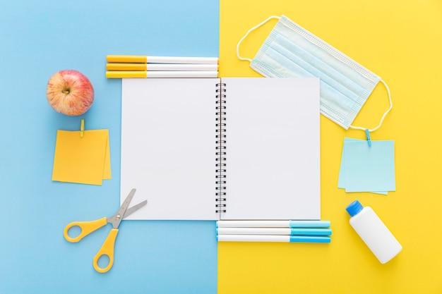 Colocación plana de materiales de regreso a la escuela con cuaderno y manzana