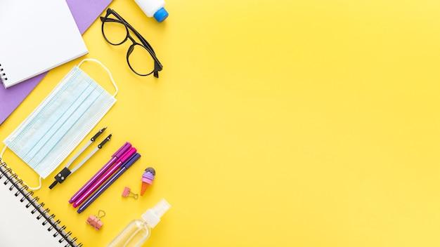 Colocación plana de materiales de regreso a la escuela con gafas y mascarilla