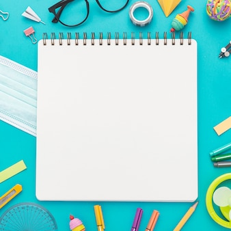Colocación plana de materiales de regreso a la escuela con lápices y cuaderno