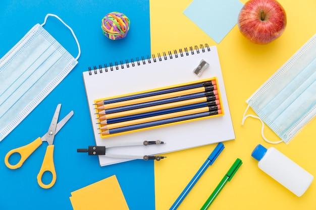 Colocación plana de materiales de regreso a la escuela con lápices y tijeras.