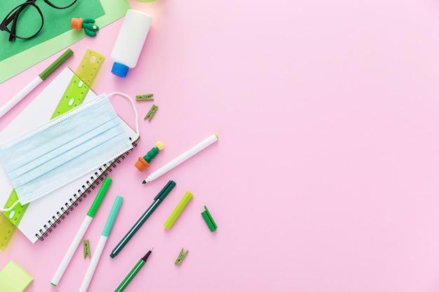 Colocación plana de materiales de regreso a la escuela con mascarillas y lápices