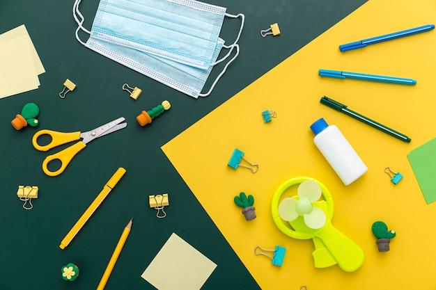 Colocación plana de materiales de regreso a la escuela con tijeras y mascarillas