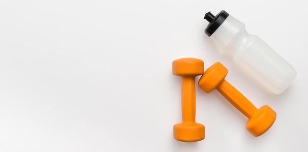 Colocación plana de pesas naranjas con botella de agua y espacio de copia