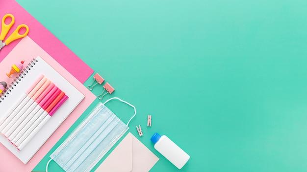Colocación plana de suministros de regreso a la escuela con mascarilla y lápices