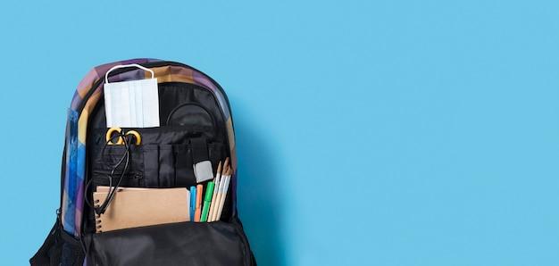 Colocación plana de suministros de regreso a la escuela en una mochila con espacio de copia