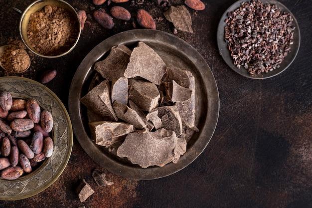 Colocación plana de trozos de chocolate en un plato con granos de cacao y polvo