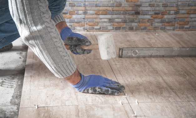 Colocación de suelo de baldosa cerámica. renovando el piso
