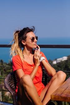 Colocar bronceada tatuada mujer europea caucásica con cuerpo deportivo y abs, en pantalones cortos de jean y camiseta roja naranja