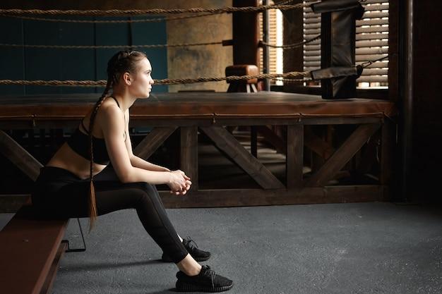 Colocar chica que descansa después de un entrenamiento de cardio intensivo en el gimnasio. retrato de lado de cansado serio joven boxeadora en zapatillas negras y ropa deportiva relajante en un banco