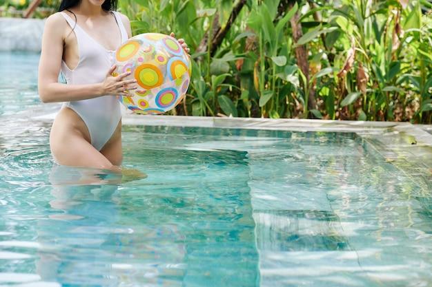 Colocar delgada joven de pie en la piscina con pelota inflable en las manos