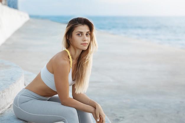 Colocar deportista activa saludable joven entrenador físico femenino caucásico sentado escaleras de hormigón disfrutando del atardecer