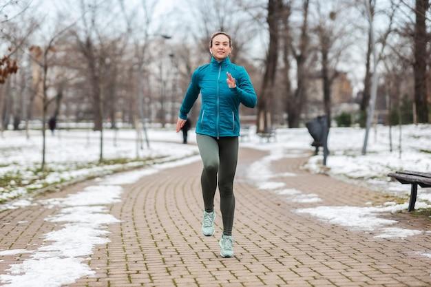 Colocar deportista corriendo en el camino en el parque en un día nevado de invierno. recreación, clima nevado, día de invierno