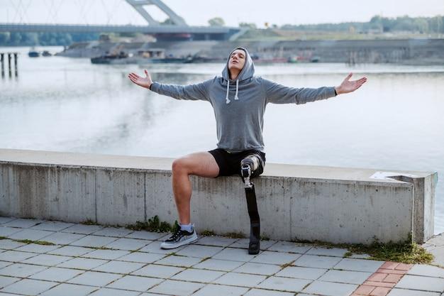 Colocar deportista discapacitado caucásico sano con pierna artificial y sudadera con capucha en la cabeza sentado en el muelle con los brazos abiertos.