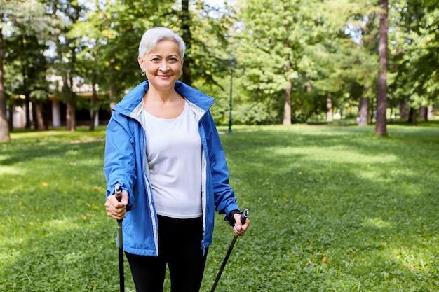 Colocar feliz mujer madura de pelo gris en ropa deportiva disfrutando de actividad física promotora de la salud utilizando bastones para caminar con expresión facial alegre y emocionada, respirando aire fresco en la naturaleza salvaje, sonriendo
