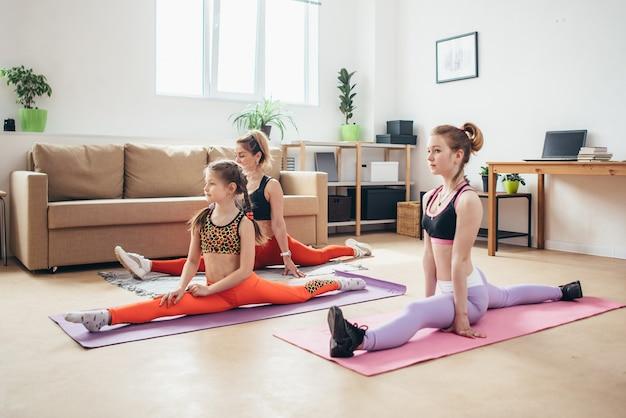 Colocar hembras haciendo divisiones. madre e hijas haciendo ejercicio, estirando las piernas.