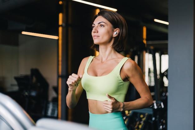 Colocar hermosa mujer caucásica en ropa deportiva adecuada en el gimnasio corriendo trotar en cinta con auriculares inalámbricos en los oídos