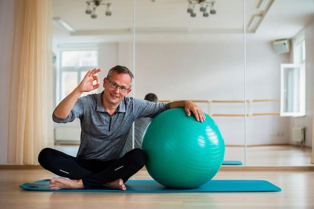 Colocar hombre adulto de pie junto a la pelota de ejercicios