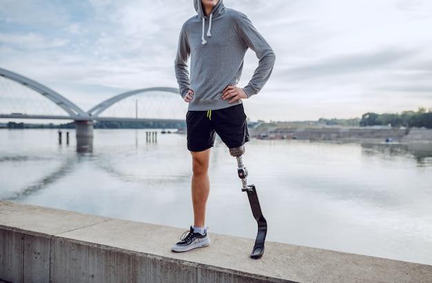 Colocar a hombre discapacitado caucásico sano en ropa deportiva y con pierna artificial de pie en el muelle con las manos en las caderas.