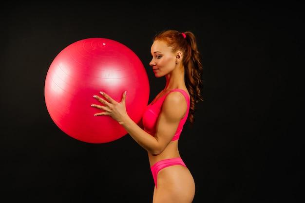 Colocar joven ejercicio con pelota de fitness sobre fondo oscuro
