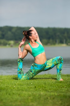 Colocar joven mujer practicando yoga al aire libre en el parque