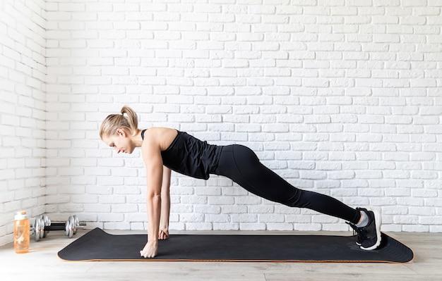 Colocar joven mujer en ropa deportiva negra haciendo flexiones en casa