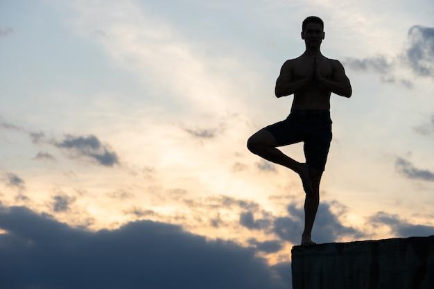 Colocar joven practica yoga saludo al sol en el borde del acantilado al atardecer.