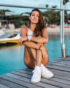 Colocar morena bronceada mujer tatuada en pantalones cortos de jean azul claro y top blanco se sienta en el muelle de madera a la luz del atardecer