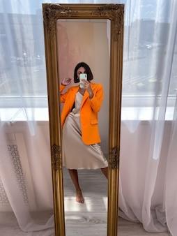 Colocar mujer bronceada en un romántico vestido de seda beige y una chaqueta naranja en casa toma una foto selfie en el teléfono en el espejo