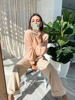 Colocar mujer bronceada en suéter melocotón y pantalón beige clásico en casa tomando selfie foto