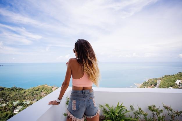 Colocar mujer caucásica bronceada en top deportivo y pantalones cortos de jean en el balcón de la villa de lujo con vista al mar tropical disfrutando de sus vacaciones, posando para la cámara