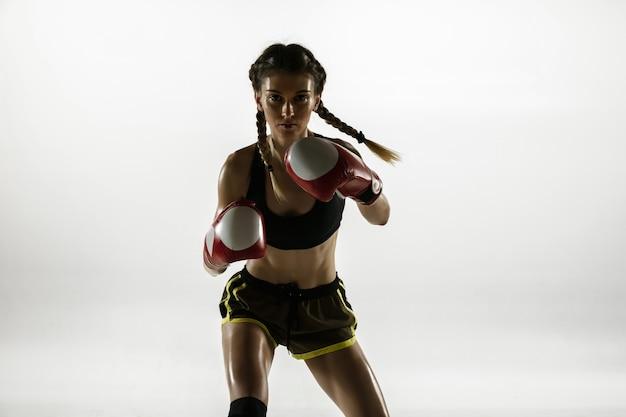 Colocar mujer caucásica en ropa deportiva de boxeo aislado en la pared blanca. boxeador caucásico femenino novato entrenando y practicando en movimiento y acción. deporte, estilo de vida saludable, concepto de movimiento.