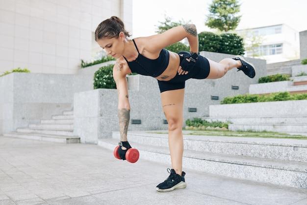 Colocar mujer joven inclinada hacia adelante con mancuerna en mano y levantando la pierna opuesta y trabajando en sus glúteos