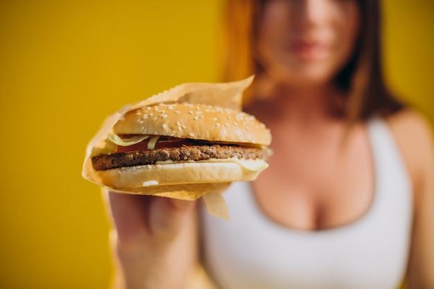 Colocar mujer en ropa deportiva comiendo hamburguesa aislado sobre fondo amarillo