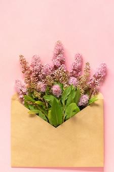 Coloque las flores rosadas en un sobre de artesanía sobre un fondo rosado. tarjeta de felicitación. lay plano. espacio de copia. concepto hola primavera.