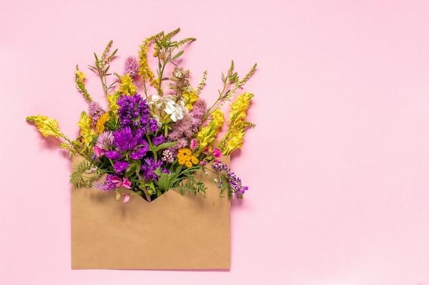 Coloque las flores rústicas coloridas en sobre del arte en tarjeta de felicitación rosada del fondo
